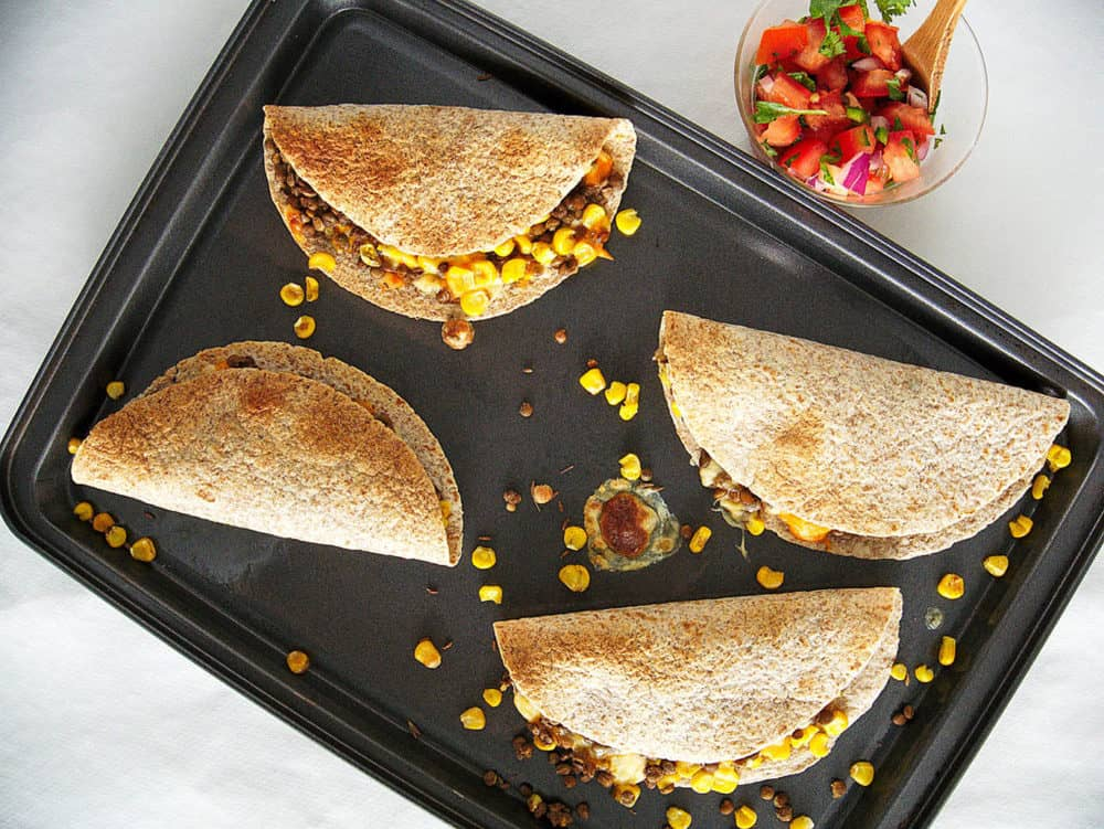 vegetarian quesadillas with cumin and lentils - pictured on a baking sheet, fresh out of the oven - top view