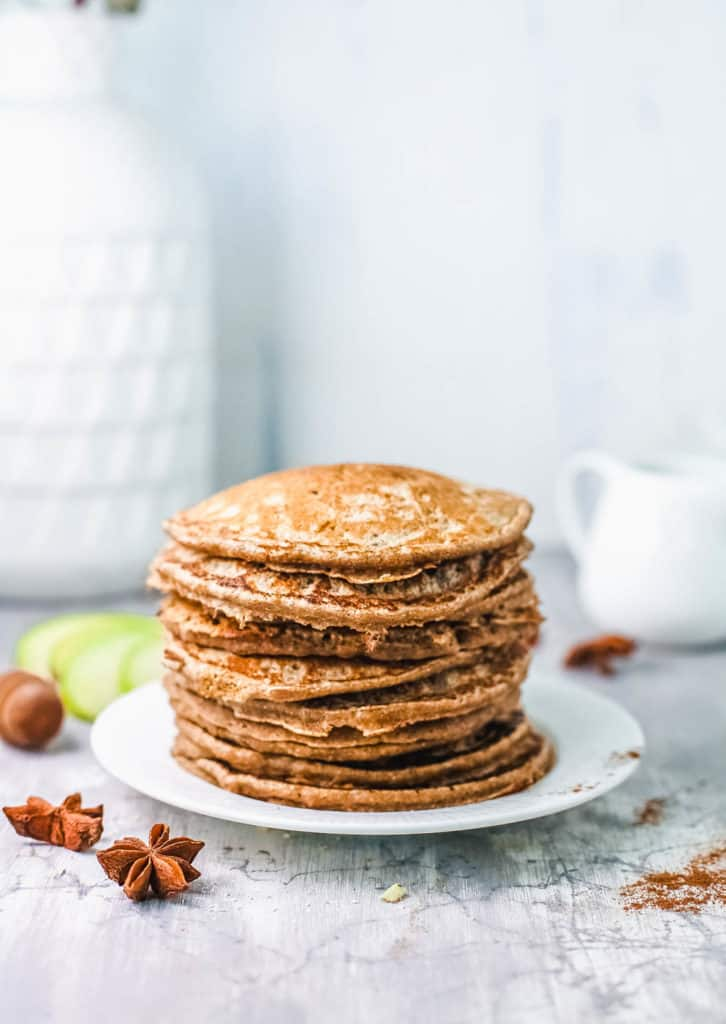 stacked apple cinnamon pancakes on white plate