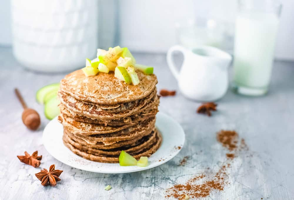 stacked apple cider pancakes on white plate, with diced apple compote on top