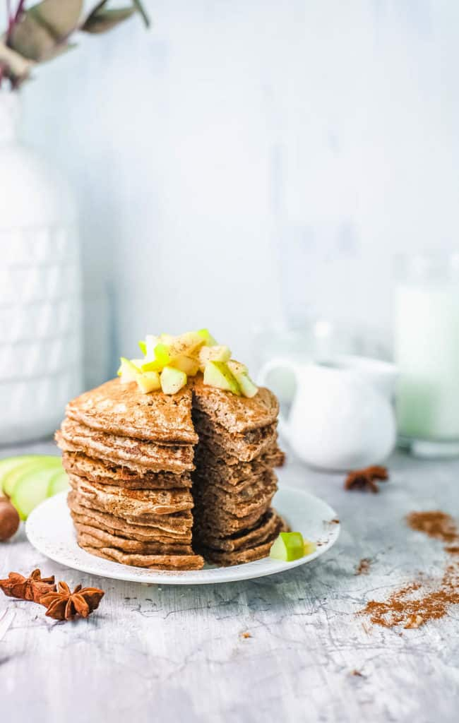 stacked apple cinnamon pancakes on white plate, with diced apple compote on top, cut into with a knife