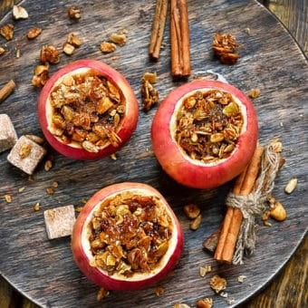 baked apples stuffed with spiced sprouted quinoa, granola, nuts, fruit - top view on a grey plate