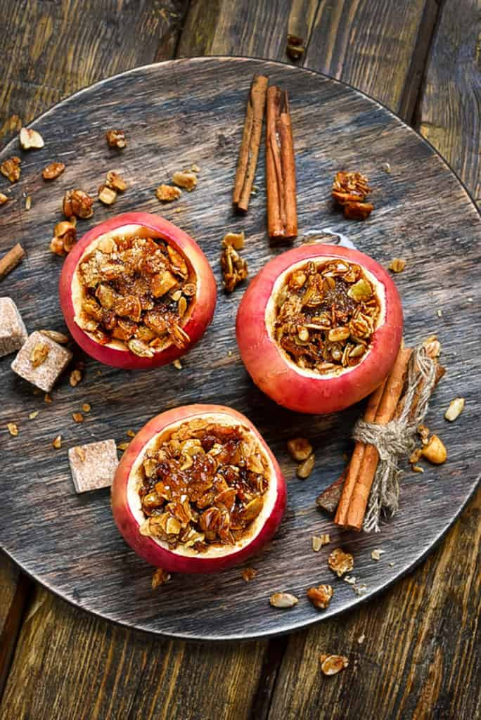 baked cinnamon apples stuffed with spiced sprouted quinoa, granola, nuts, fruit - top view on a grey plate