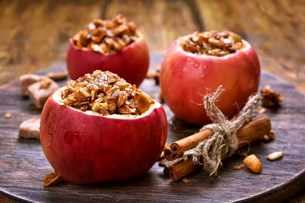 baked cinnamon apples stuffed with spiced sprouted quinoa, granola, nuts, fruit - on a grey plate