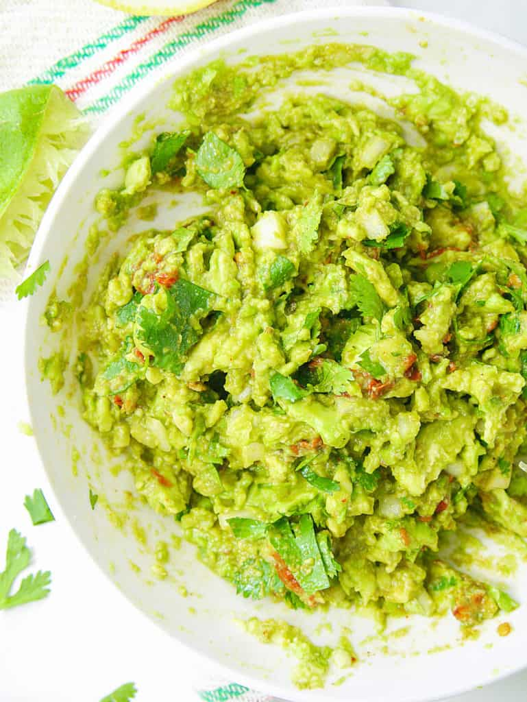 healthy guacamole recipe served in a white bowl, top view