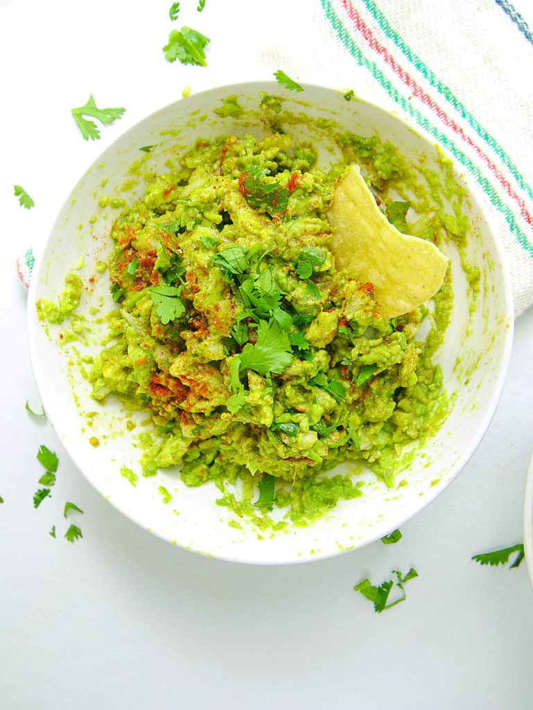 healthy guacamole recipe in bowl with chip
