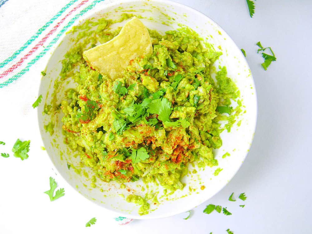healthy guacamole recipe in bowl with chip, top view