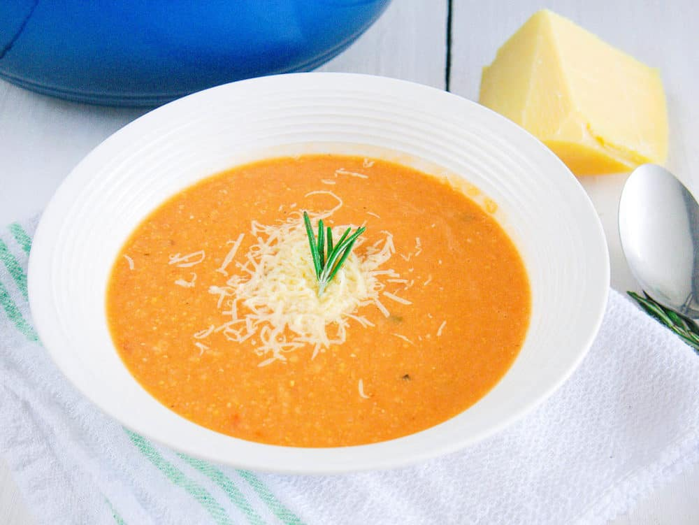 italian chickpea soup in a white bowl topped with parmesan cheese
