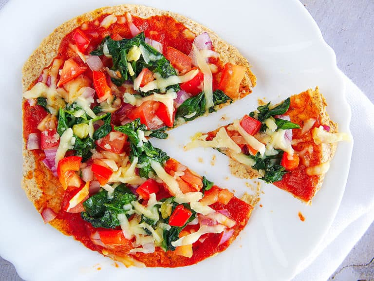 healthy vegetarian flatbread topped with fresh veggies, served on a white plate