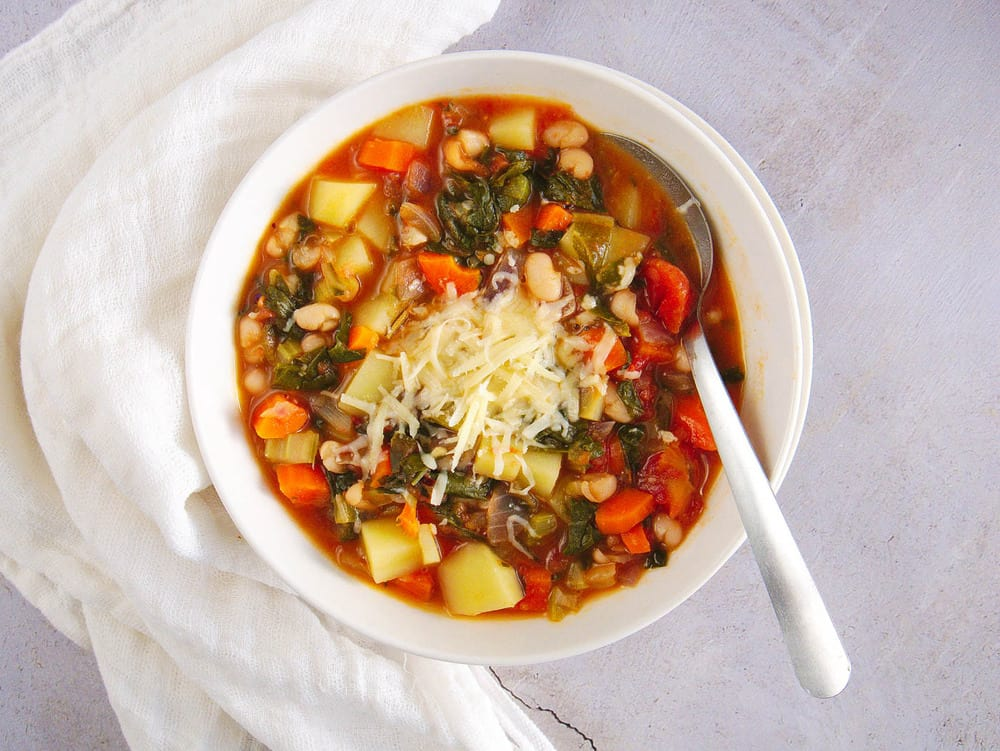 healthy minestrone soup, served in a white bowl, top view