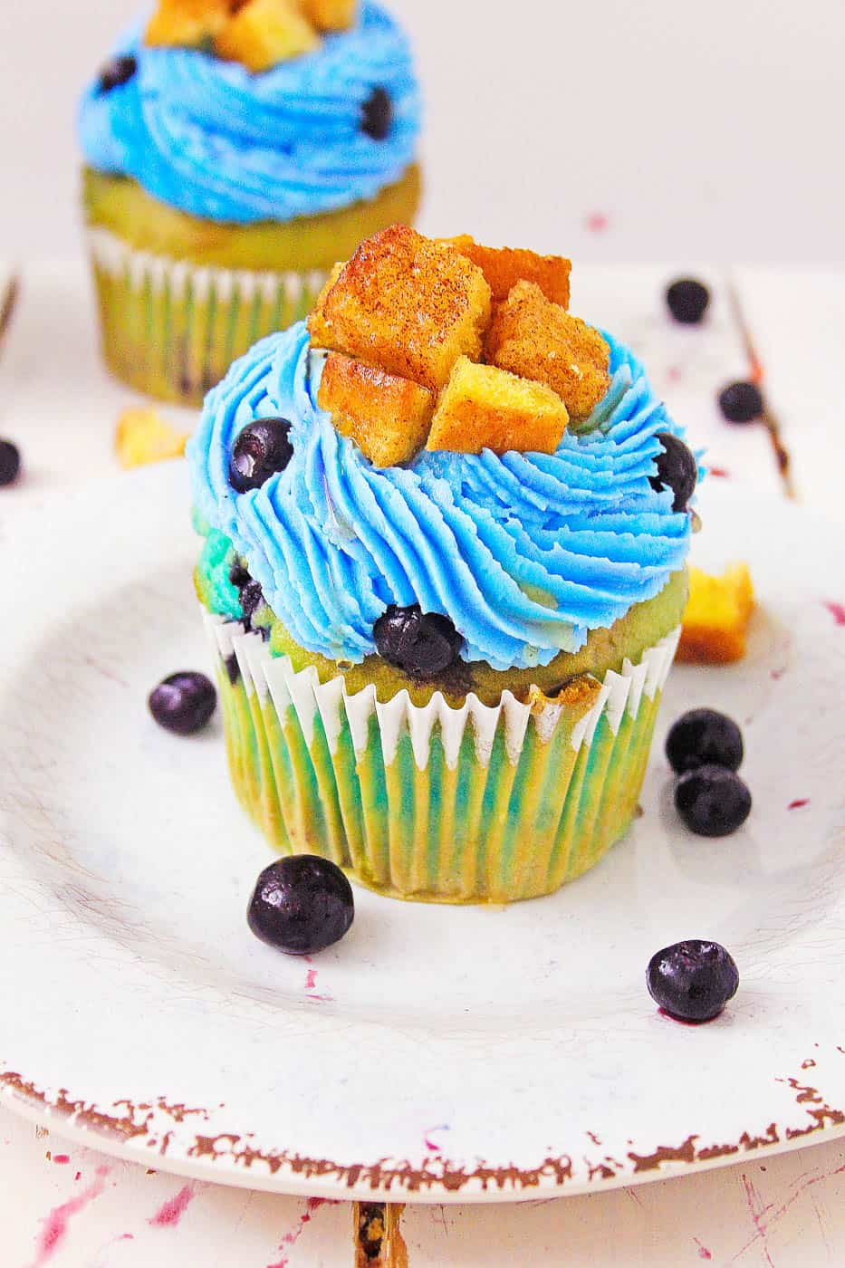 healthy Blueberry Lemonade Cupcakes With Lemon Cream Cheese Frosting on a white plate topped with french toast and fresh blueberries
