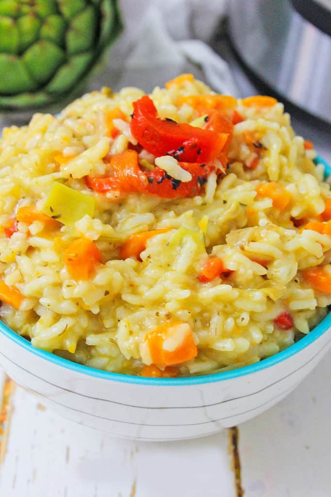instant pot risotto with artichokes and red peppers in white bowl