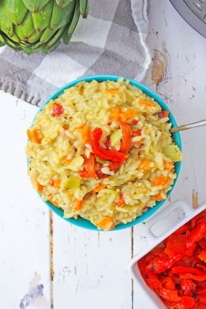 Instant pot risotto with roasted red peppers and artichokes, served in a bowl, top view