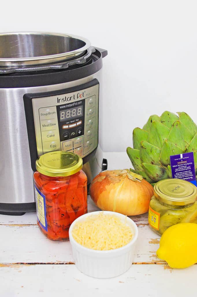 instant pot risotto ingredients (artichokes, roasted red peppers, onion, cheese, etc. next to the instant pot)