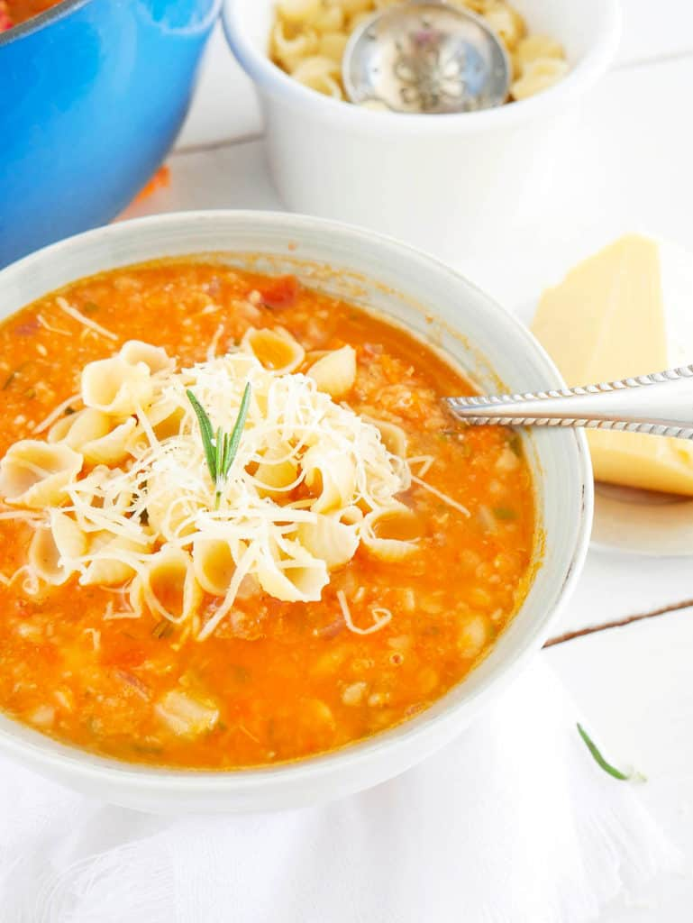 Chunky and Hearty Pinto Bean Soup in a white bowl, topped with parmesan cheese and pasta shells