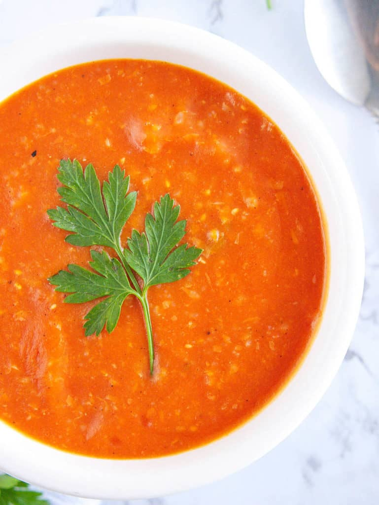 roasted vegan tomato soup topped with fresh herbs in a white bowl against a marble background, top view