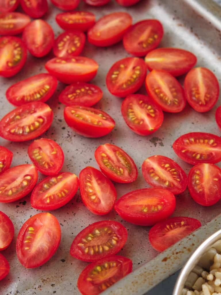 grape tomatoes sliced on a baking sheet