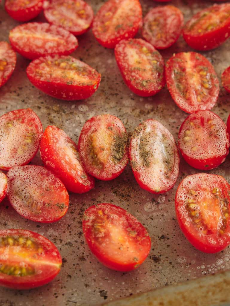 grape tomatoes sliced on a baking sheet with salt/pepper