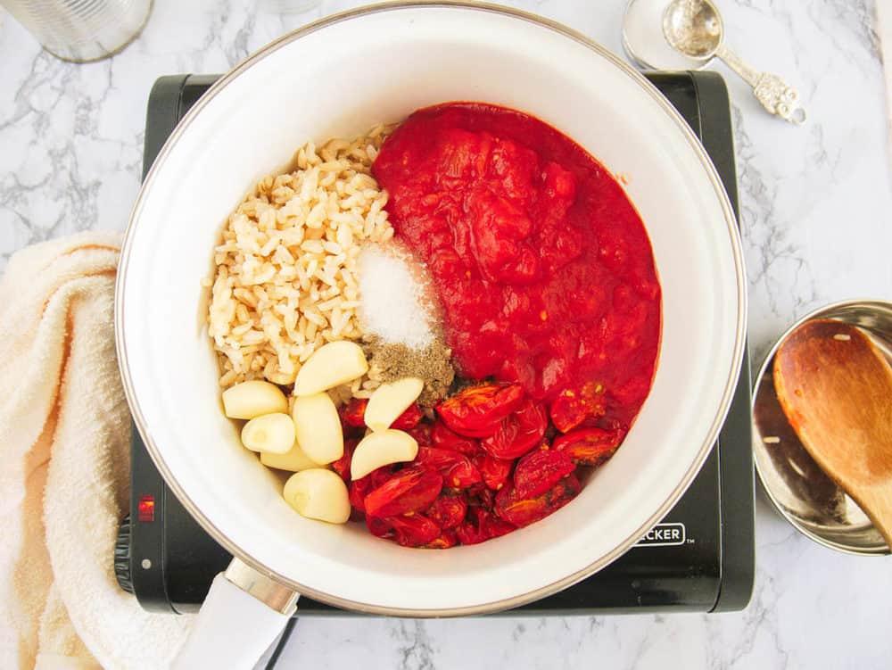 garlic, tomatoes, rice, seasonings in a pot