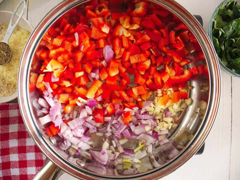 peppers onions and garlic being sauteed in a pan