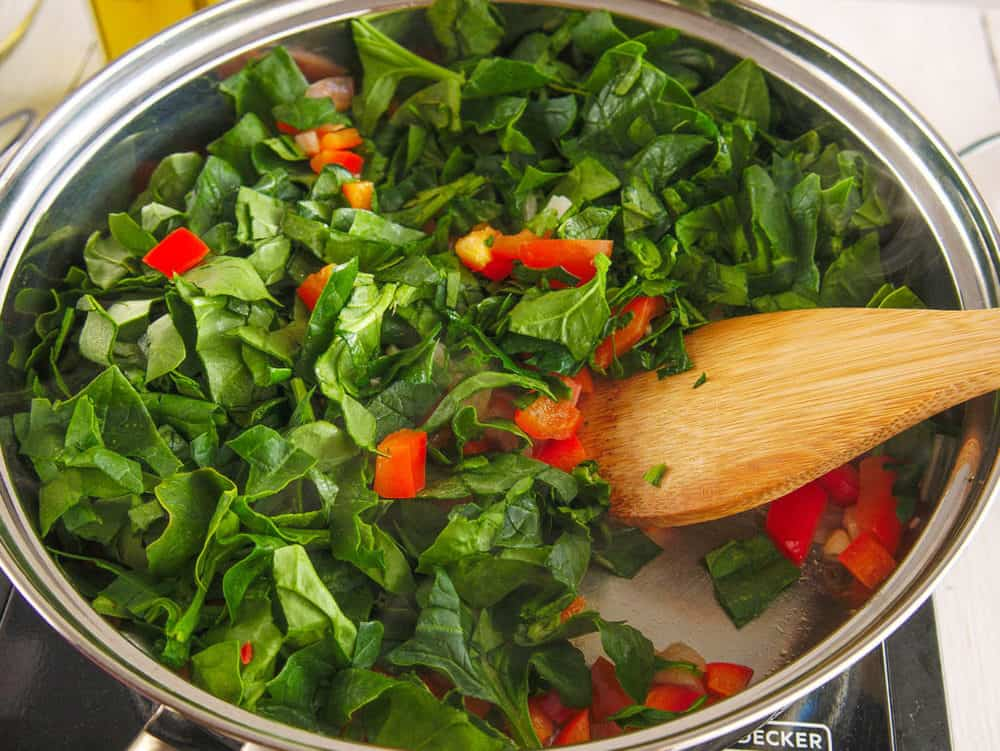 spinach added to pan with garlic peppers onions