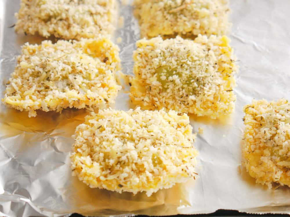 coated raviolis on baking sheet