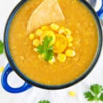 potato corn chowder - spicy, dairy-free, served in a blue bowl with fresh corn, tomatoes, and a corn chip as garnishes