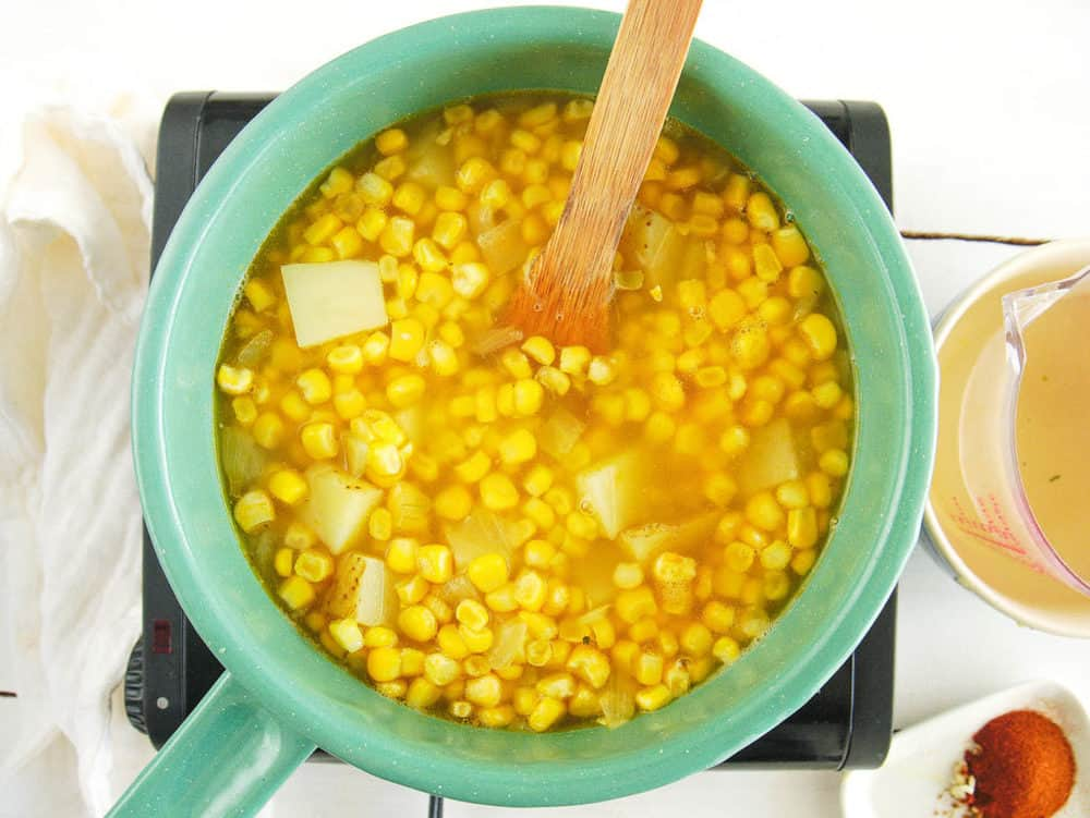 corn added to pot with potatoes and broth