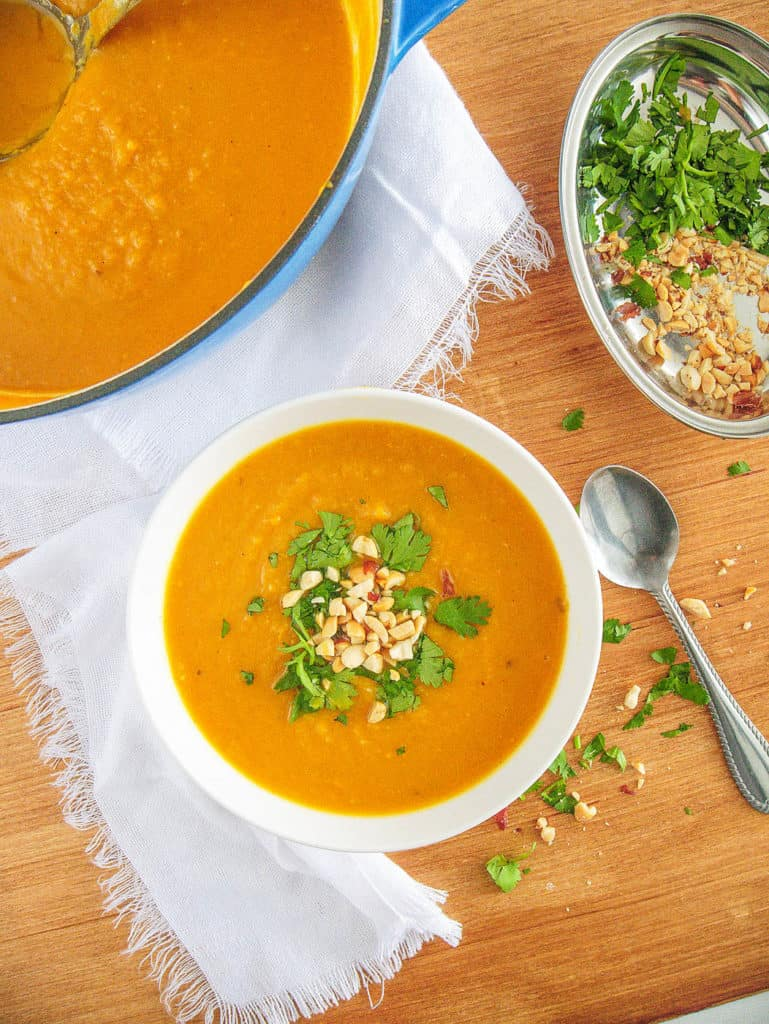 spicy sweet potato soup served in a white bowl, topped with crushed nuts and cilantro