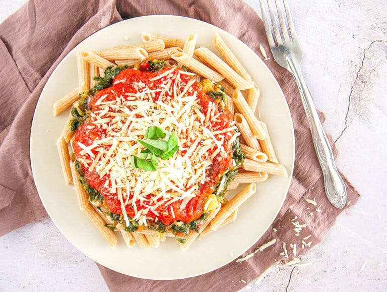 whole wheat pasta recipe topped with spinach, pasta sauce, parmesan cheese on a white plate, with a fork