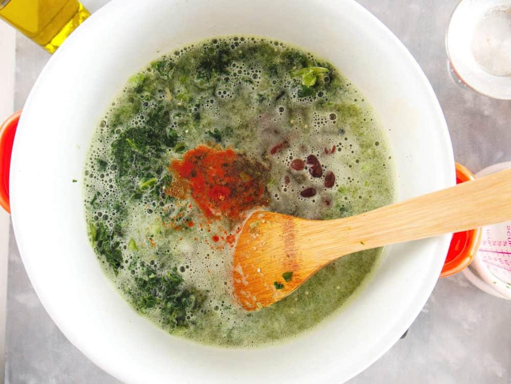ingredients for vegetarian black bean stew simmering in a pot