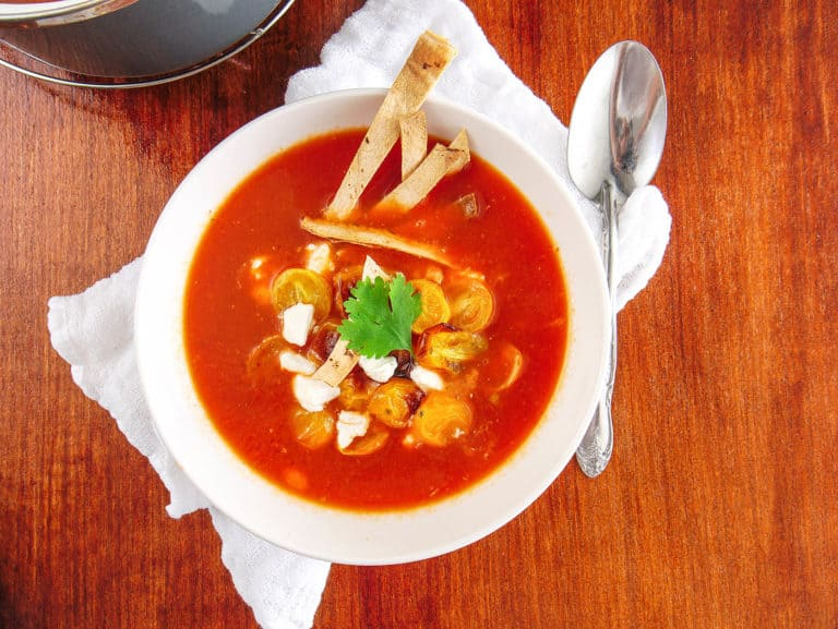 vegetarian taco soup served in a white bowl, topped with tomatoes goat cheese tortilla chips and cilantro