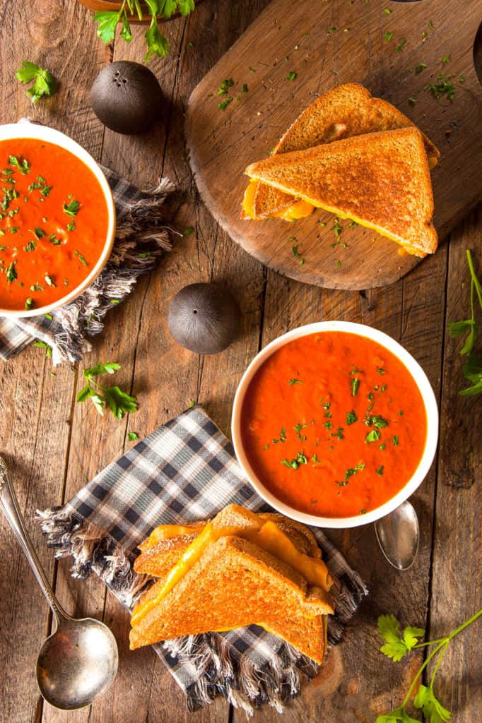 instant pot tomato soup pictured in a white bowl against a wooden background with a grilled cheese sandwich on the side