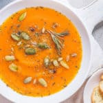 vegetarian white bean soup with pumpkin, served in white bowls, topped with pumpkin seeds