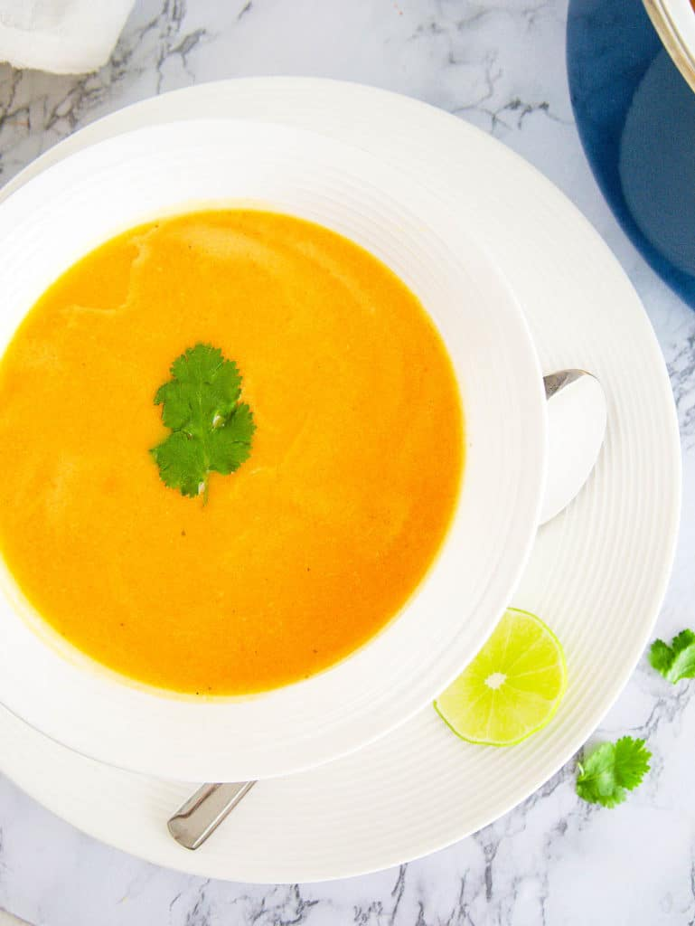 acorn squash bisque served in a white bowl with fresh herbs on top, top view