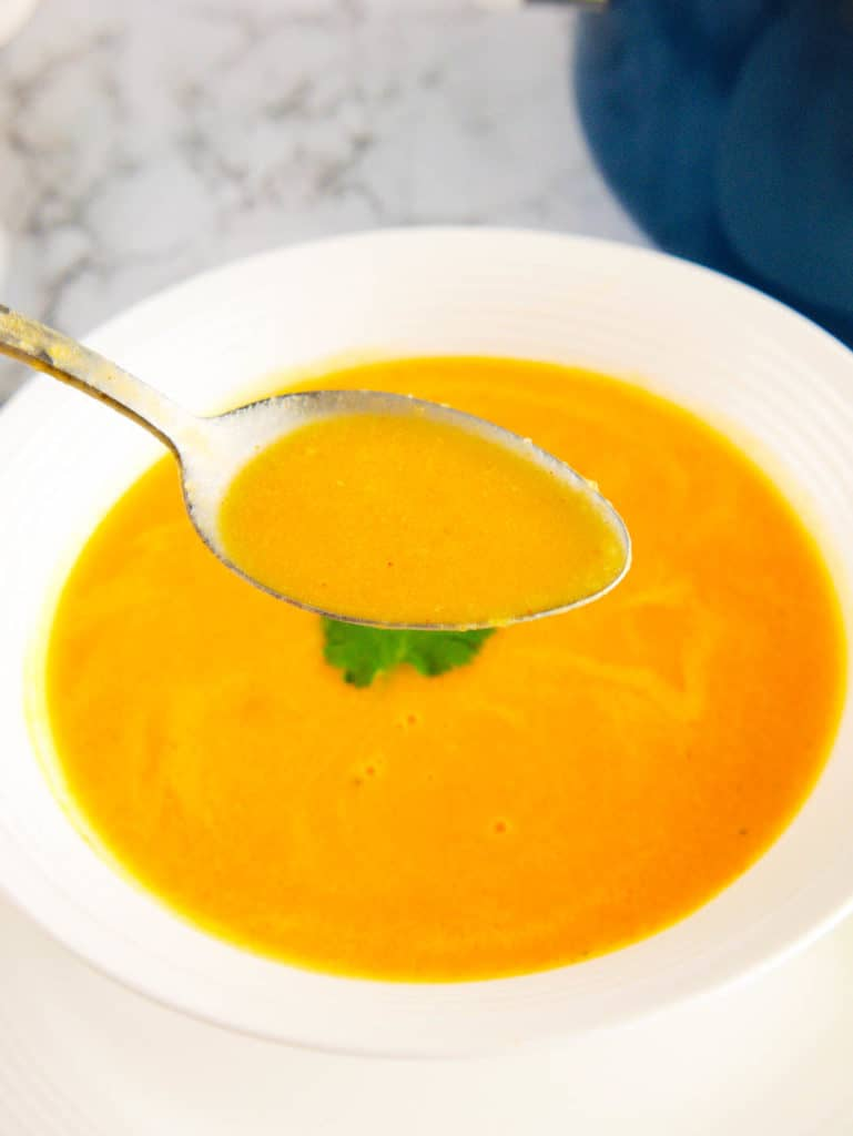 spoonful of acorn squash bisque served in a white bowl with fresh herbs on top