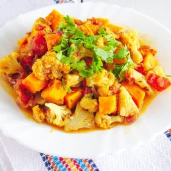 roasted cauliflower curry with sweet potatoes topped with cilantro, served on a white plate
