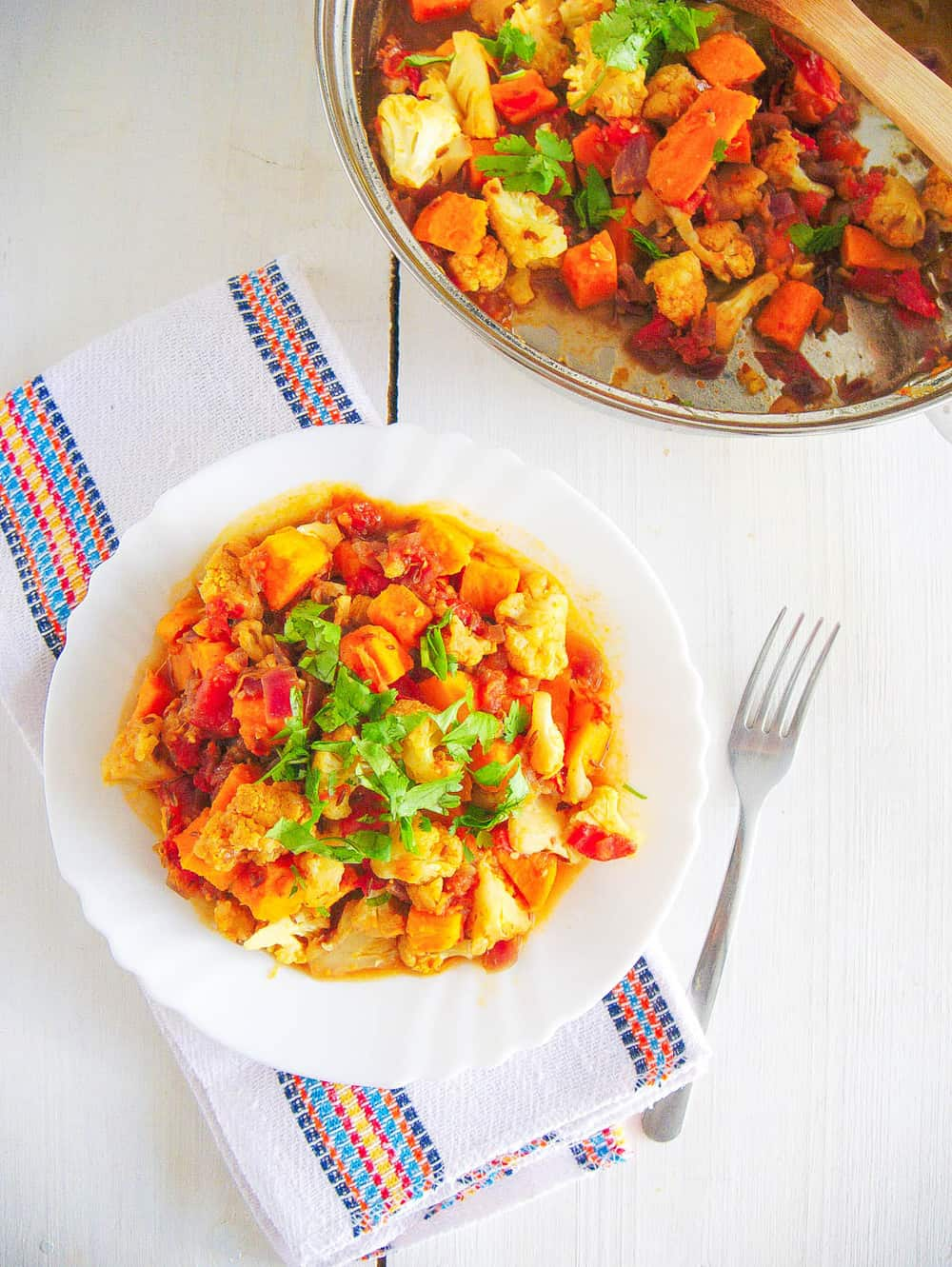 sweet potato cauliflower curry with sweet potatoes topped with cilantro, served on a white plate