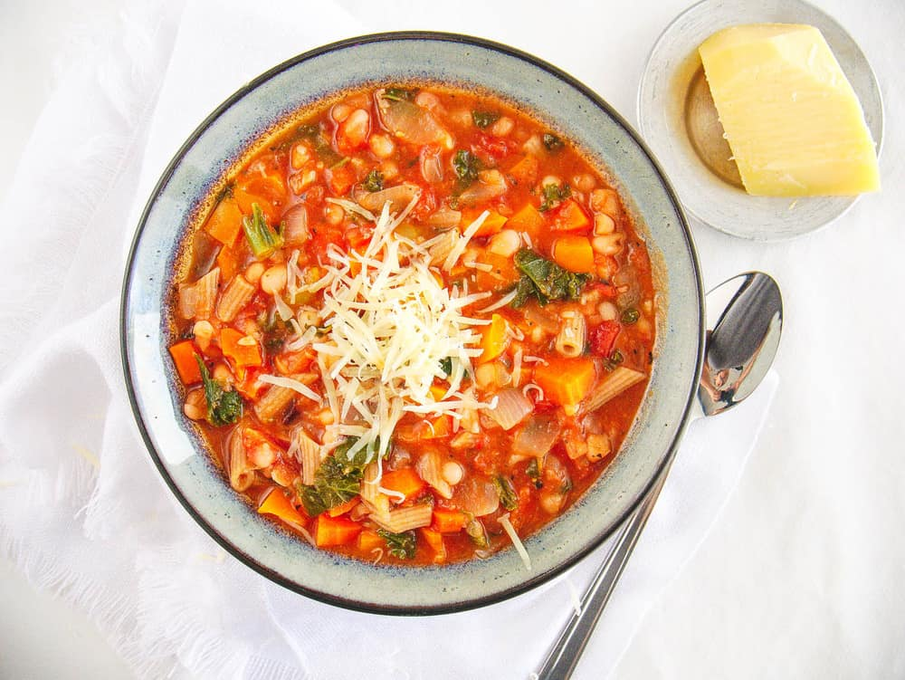 Tuscan Bean Stew with Whole Wheat Pasta, topped with parmesan cheese and served in a ceramic bowl
