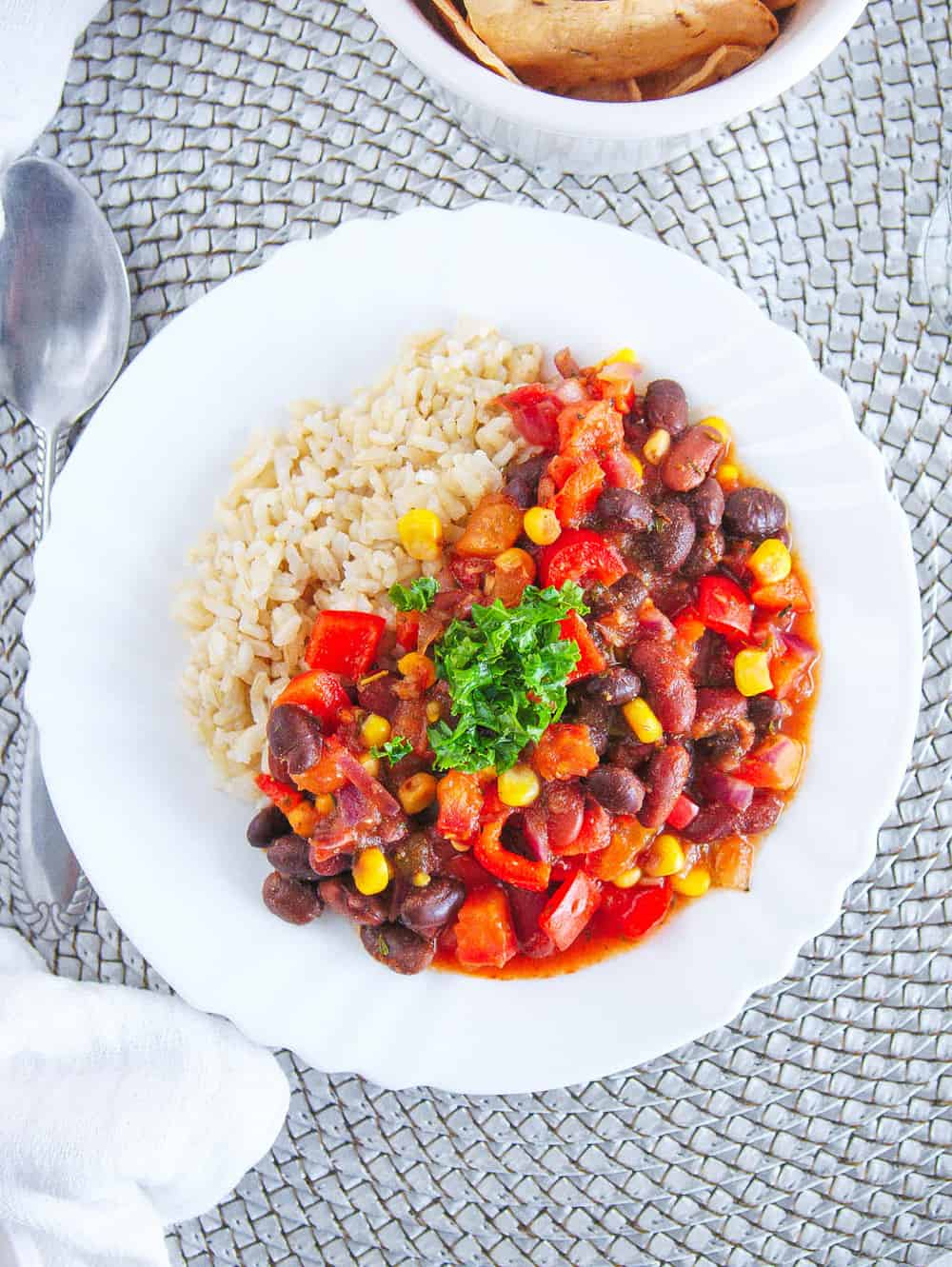 vegetarian stew recipe with beans and rice, served on a white plate with a spoon