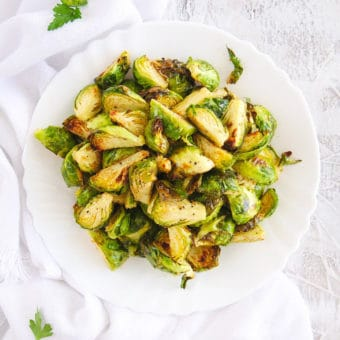 air fryer brussel sprouts served on a white plate, top view