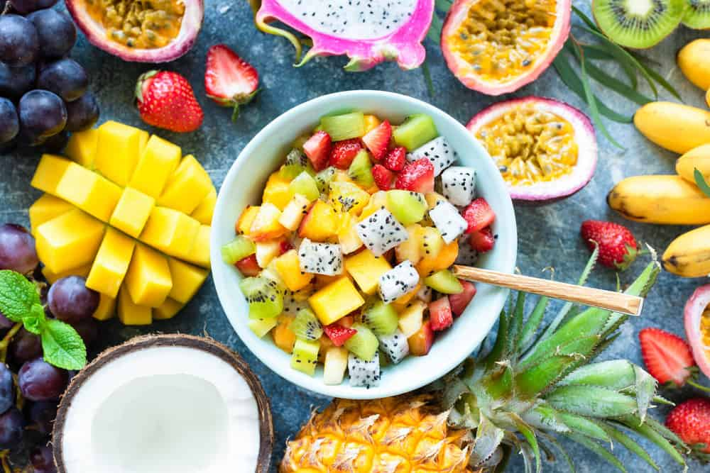 Mexican Fruit Salad with cubed melon, mango, jicama, dragon fruit, lime juice, and a hint of spicy chili - served in a blue bowl