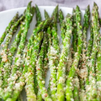 steamed asparagus with pecorino, served on a white plate