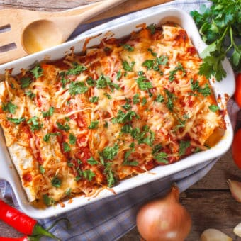 vegetarian enchilada casserole, in a baking dish with the ingredients on the table