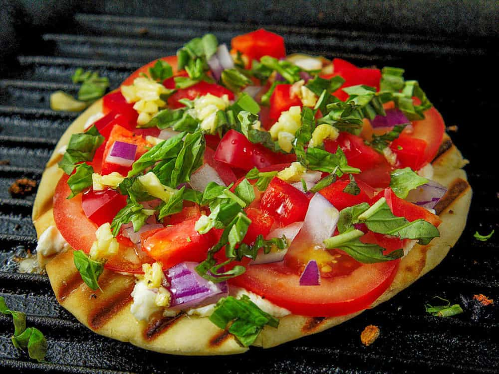 pita pizza with toppings cooking on a grill
