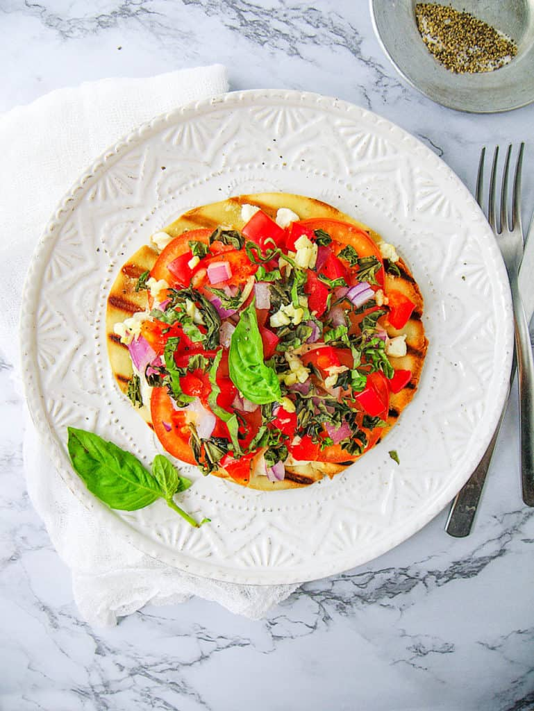 healthy pita pizza with goat cheese and tomatoes, served on a white plate, garnished with basil