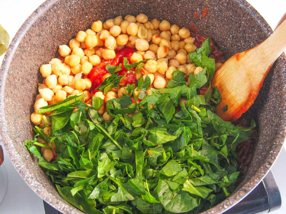 chickpeas tomatoes greens added to pot