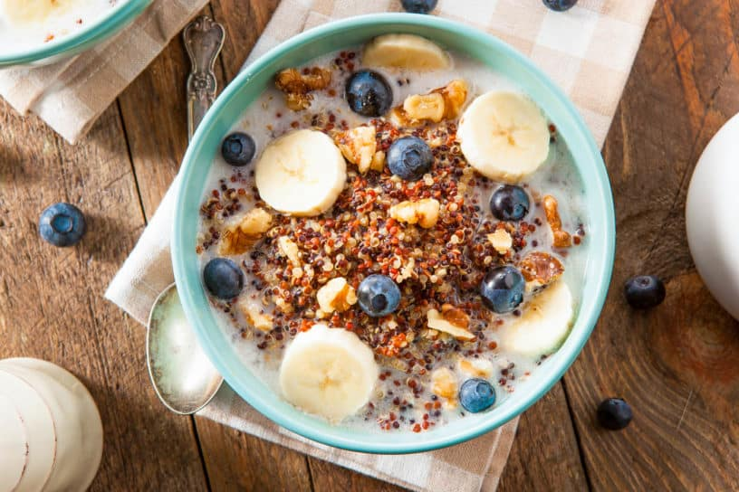 Quinoa Oatmeal with Nuts Milk and Berries, served in a blue bowl