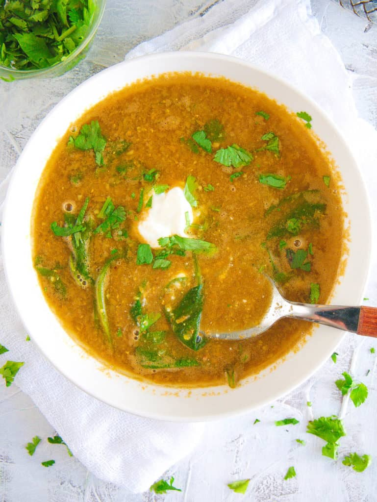 lebanese lentil soup with spinach, served in a white bowl with cilantro on top