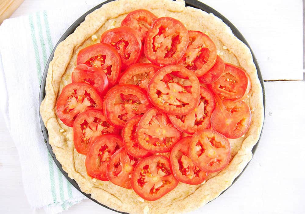 pizza dough topped with olive oil, garlic, tomatoes