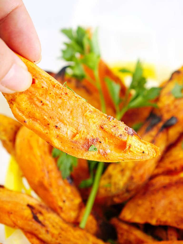 closeup of air fried sweet potato fries in a yellow basket